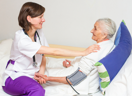 Photo pour Happy joyful nurse caring for  an elderly woman  helping her days in nursing home. - image libre de droit