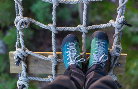 Foto de outdoor shoes on a rope grid , in an adventure park - Imagen libre de derechos