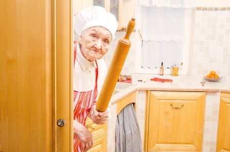 Photo pour Funny elderly lady hiding in the kitchen with rolling pin in hand. - image libre de droit