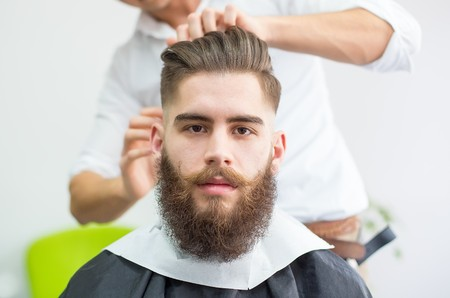Photo pour Hipster guy getting ready for the shooting at the barber. - image libre de droit