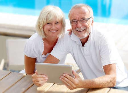 Foto de Different aged couple using a Tablet PC outside on the pool - Imagen libre de derechos