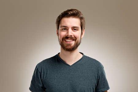 Foto de Portrait of smiling young man with beard, on neutral background - Imagen libre de derechos
