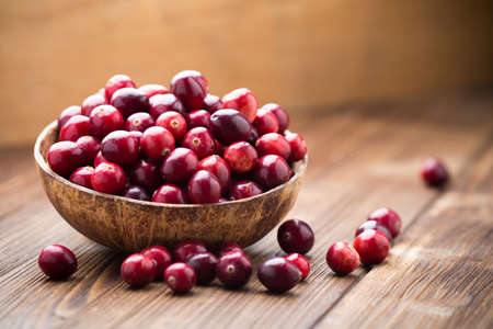 Photo for Cranberries in wooden bowl on wooden background. - Royalty Free Image