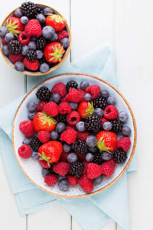 Photo for Fresh berries salad in a plate on a  wooden background. Flat lay, top view, copy space. - Royalty Free Image