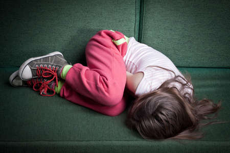 Photo for little girl curled up in fetal position on a couch protecting herself from danger or cold - Royalty Free Image