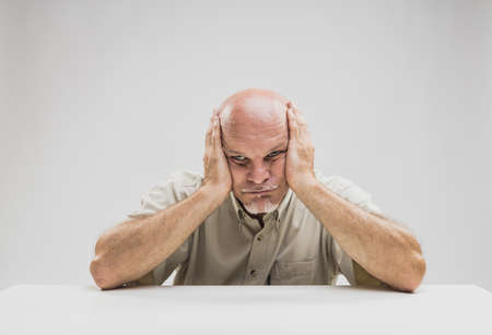 Foto de Bored senior man with a glum despondent expression sitting at a table staring straight ahead with his head in his hands - Imagen libre de derechos