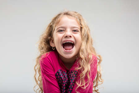 Photo for Portrait of laughing preteen girl with curly hair against plain background - Royalty Free Image