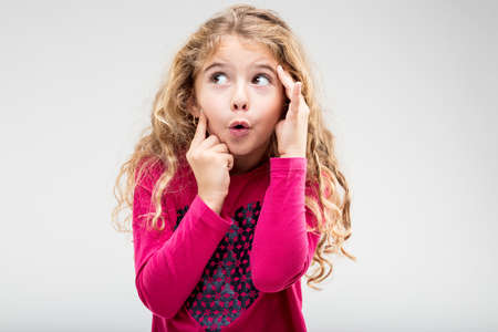 Foto de Fun playful little blond girl with a teasing expression exclaiming Ooh holding her hands to her head as she glances up to the side - Imagen libre de derechos