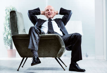 Photo for Businessman sitting relaxing and de-stressing in a comfortable armchair with his leg draped over the side, hands behind his neck, eyes closed and a happy smile - Royalty Free Image