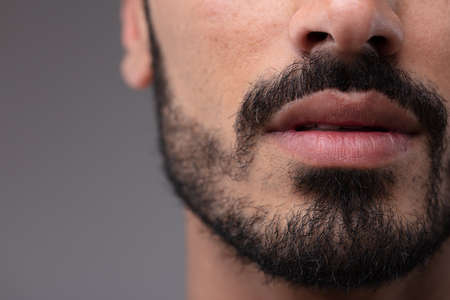 Foto de Close up on the mouth and chin of a bearded man in a cropped view of his face over a grey background - Imagen libre de derechos