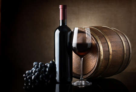 Photo pour Bottle of red wine, grapes and wooden barrel - image libre de droit