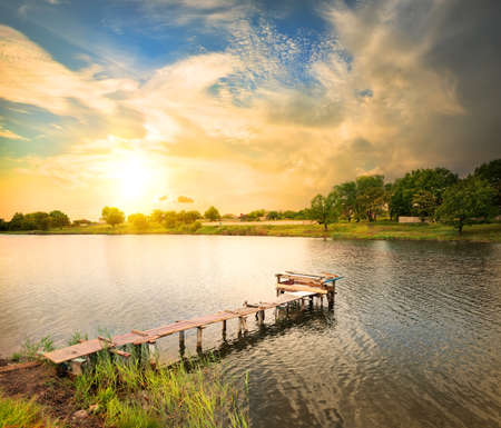 Photo for Wooden dock, pier, on a lake in the evening - Royalty Free Image