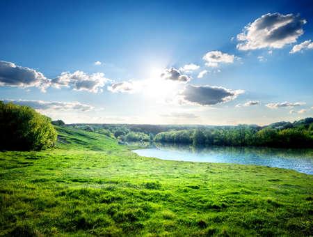 Photo pour Green lawn near river in the forest - image libre de droit