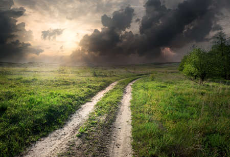 Photo pour Lightning and storm clouds over country road - image libre de droit