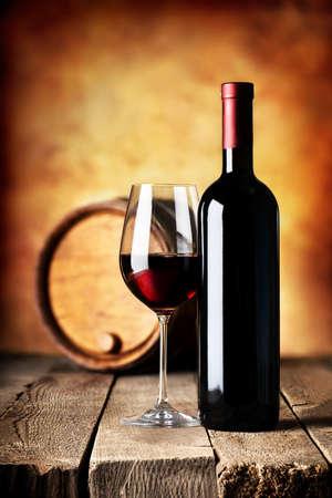 Foto de Red wine in bottle and cask on a wooden table - Imagen libre de derechos
