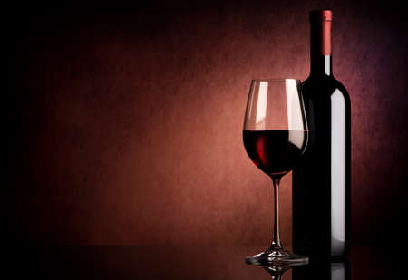 Photo pour Red wine in bottle and wineglass on vinous background - image libre de droit