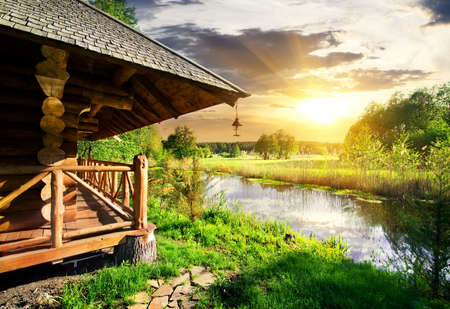 Foto de Wooden bathhouse near lake at the sunset - Imagen libre de derechos
