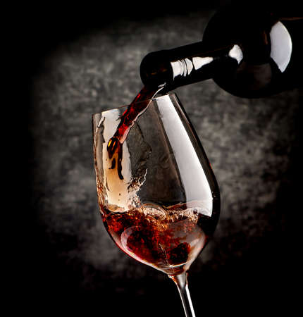 Photo pour Wine pouring in wineglass on a black background - image libre de droit