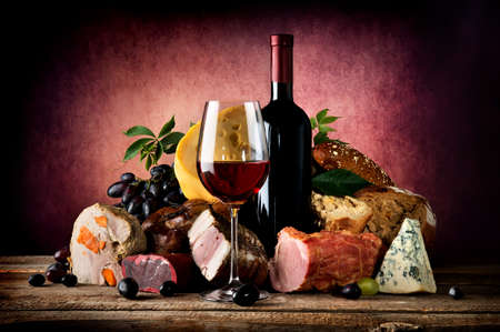 Photo pour Red wine and different food on a wooden table - image libre de droit