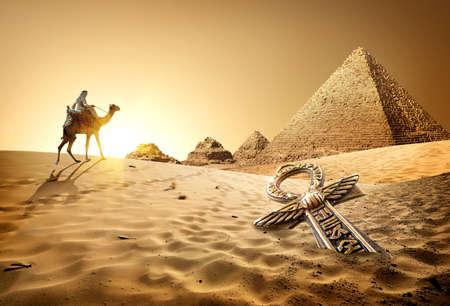 Photo pour Bedouin on camel near pyramids and ankh in desert - image libre de droit