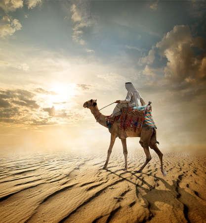 Foto de Bedouin rides on camel through sandy desert - Imagen libre de derechos