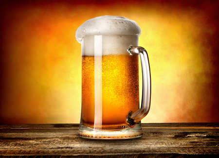 Foto de Beer in mug on wooden table and yellow background - Imagen libre de derechos