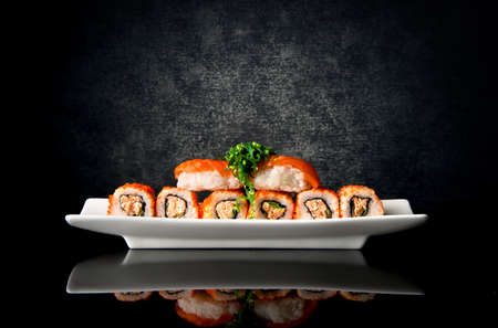 Photo pour Sushi and rolls in plate on a black background - image libre de droit
