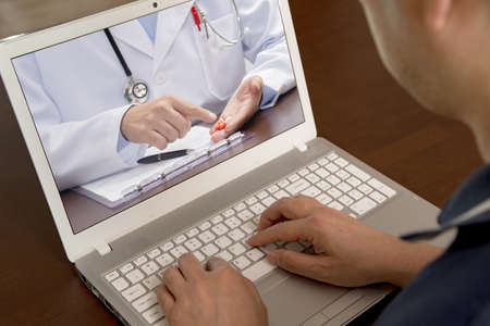 Foto de A middle-aged man who uses telemedicine to listen to a doctor for medication. - Imagen libre de derechos