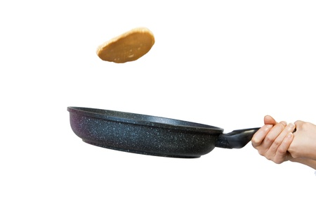 The process of flipping a pancake in a frying pan against a white background.