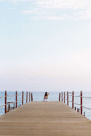 Photo for Girl sitting on the pier and looking at the sea horizon and blue sky. Vacation concept. Summer time sea vacation background - Royalty Free Image
