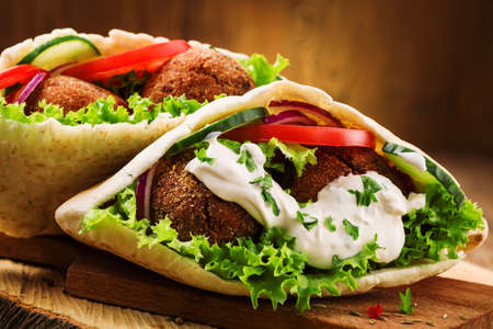 Foto de Falafel and fresh vegetables in pita bread on wooden table - Imagen libre de derechos