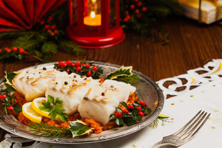 Foto de Christmas fish. Roasted cod pieces, served in vegetable sauce. Xmas styling. Front view. - Imagen libre de derechos