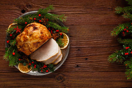 Photo for Christmas baked ham, served on the old plate. Spruce twigs all around. Top view. - Royalty Free Image