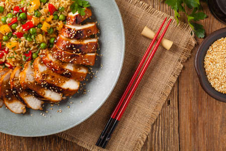 Foto de Grilled chicken breast in teriyaki sauce. Served with brown rice and vegetables. Top view. Flat lay. - Imagen libre de derechos