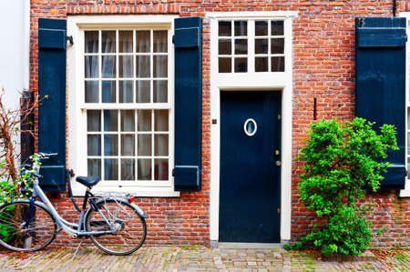 Photo pour Bike in Front of a Brick Facade of the Old Dutch House - image libre de droit