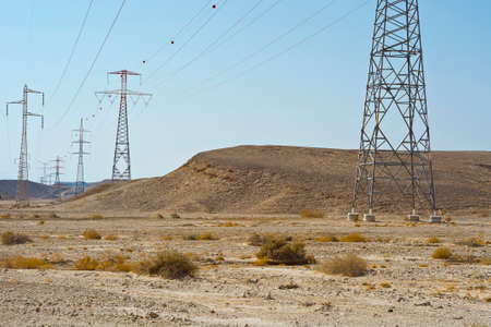 Foto de Desolate infinity of the Rocky hills of the Negev Desert in Israel. Electrical power lines on pylons in the landscape of the Middle East - Imagen libre de derechos