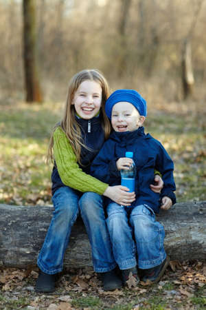 Two happy kids together with water bottle sitting on a big log in autumn forest. Happy lifestyle kids