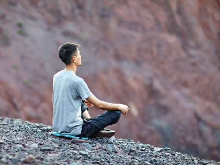 Photo pour Young young man relaxing in yoga position on rocky cliff - image libre de droit