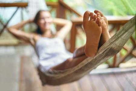 Foto de Young beautiful woman relaxing in hammock in a tropical resort. Focus on foot - Imagen libre de derechos