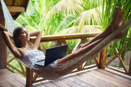 Photo pour Young beautiful woman relaxing in a hammock with laptop in a tropical resort. Break time - image libre de droit