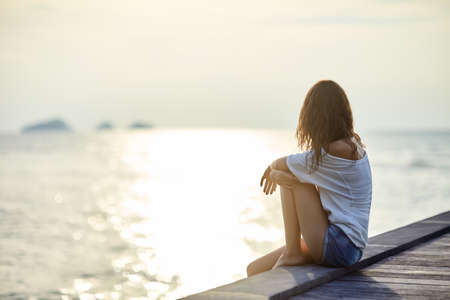 Foto de Young beautiful woman sitting on the pier enjoying sunset with copy space - Imagen libre de derechos