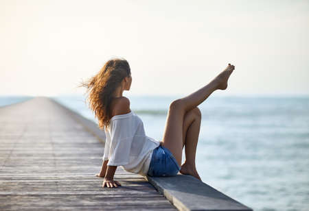 Photo for Sexy beautiful woman relaxing on pier with sea view. Vacation concept - Royalty Free Image