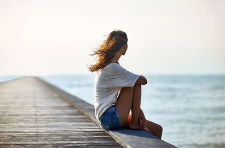 Photo pour Young beautiful woman sitting on the pier with copy space - image libre de droit