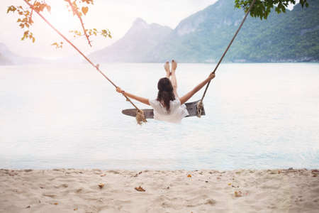 Foto de Carefree happy woman on swing on beautiful paradises beach in Thailand - Imagen libre de derechos
