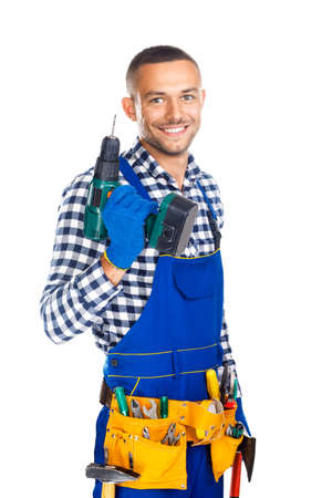 Foto de Happy smiling construction worker with drill and tool belt isolated on white background - Imagen libre de derechos