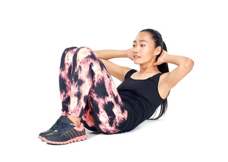 Photo for Isolated portrait of athletic slim Asian woman doing sit-ups. Fit girl doing exercises abs - workout training for abdominal muscles. Young sportswoman in sportswear. Healthy lifestyle, sport concept - Royalty Free Image