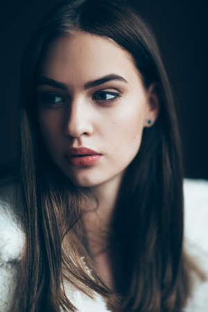 Photo for Young beautiful woman portrait, close-up. Pretty girl with red lipstick and stylish hairdo. Pensive look of the female model  - Royalty Free Image