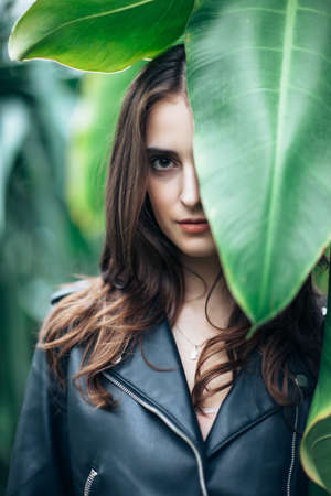 Photo for Fashion portrait of beautiful mysterious woman hide behind big leaf, close up. Girl with half closed face in greenhouse - Royalty Free Image
