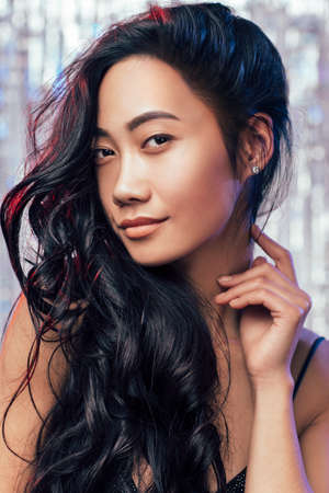 Photo pour Portrait of cute eastern girl closeup. Young brunette with curly long hair elegantly posing, smiling and touching her neck with her finger - image libre de droit