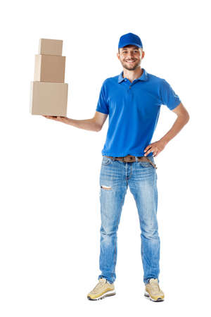 Photo for Full length portrait of smiling delivery man holding pile of cardboard boxes in one hand isolated on white background - Royalty Free Image